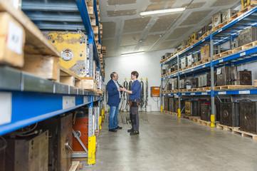 Two men examining machine blocks in storehouse