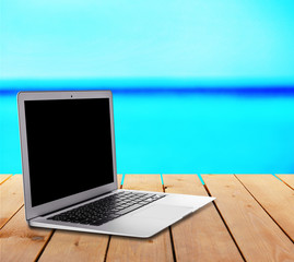 Laptop over wooden table on nature background