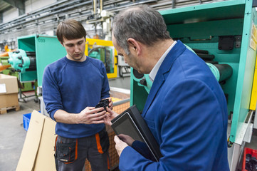 Manager and worker in plastics factory discussing production quality