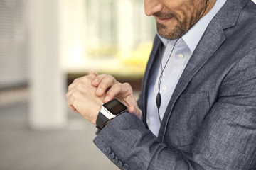 Close-up of businessman looking at smartwatch
