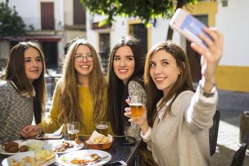 Young woman taking a selfie with her three friends at street cafe