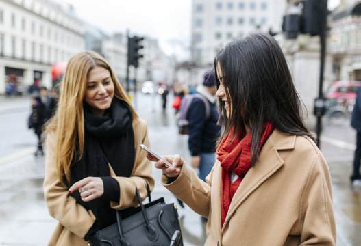UK, London, Two friends exploring the city, using smart phone