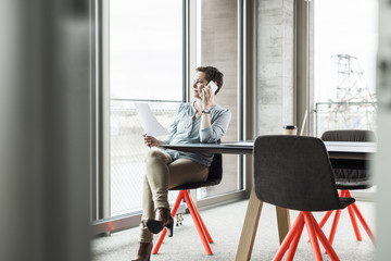 Businesswoman on cell phone in conference room