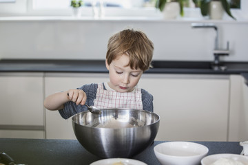 Little boy helping to prepare food in the kitchen