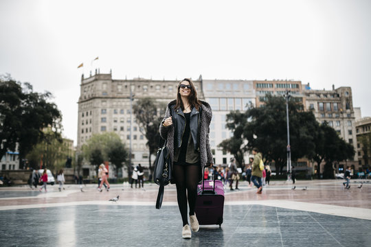 Spain, Barcelona, young woman with suitcase walking on Placa Catalunya