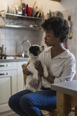 Young woman sitting in the kitchen with her dog on lap