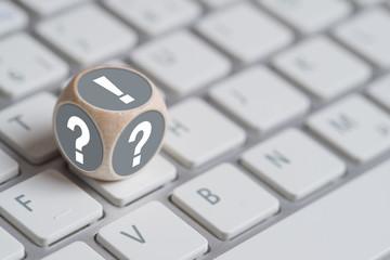 Würfel mit Fragezeichen auf den Seiten und Ausrufezeichen oben auf einer Tastatur