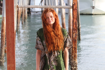 The young girl with red hair, on the tropical island, a sunny day, on a background the sea