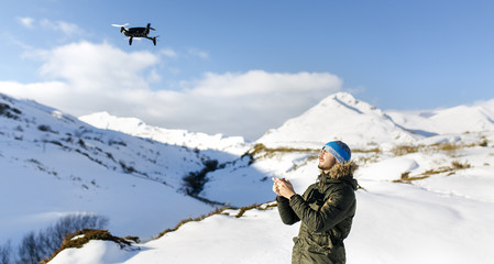 Spain, Asturias, man flying drone in snowy mountains