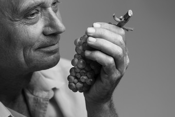 Old man holding a grape in his hand