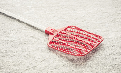 Fly swatter on stone table. Concept of exterminating bugs and insects.