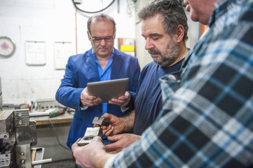 Three men with digital tablet examining workpieces