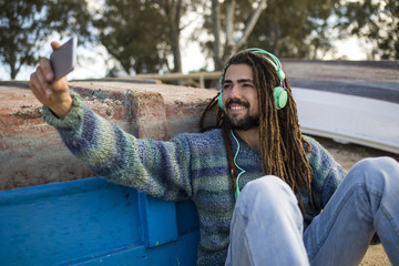 Young man with dreadlocks listening to music and using the smartphone