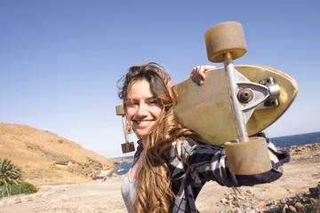 Spain, portrait of smiling teenage girl with longboard on shoulders