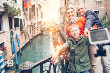 Happy family take a self photo on the bridge over Venecian chann