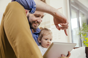 Father showing his little daughter something on digital tablet