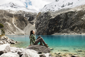 Peru, Huaraz, Huascaran National Park, woman relaxing after a trekking on lagoon, Laguna 69