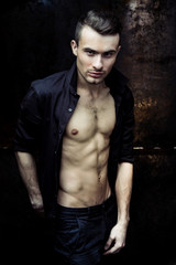 Strong Athletic Man Fitness Model Torso showing six pack abs on dark background