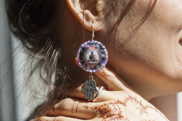 Woman wearing original earings and mehndi on her hand