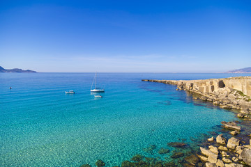Azure lagoon called Cala Rossa with yachts moored on Favignana island in Sicily, Italy