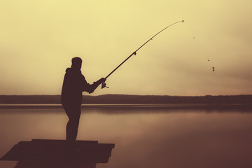 Man throws a fishing rod in the lake at evening. Back view photo.