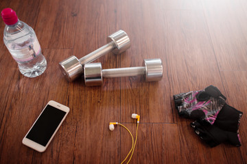 Fitness equipment accesories on wooden background, view above