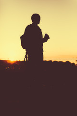 Silhouette of the person holding in hand drink in a bottle. Outdoors photo.