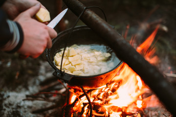 Fish soup cooking on fire in nature and the human hands cut potatoes in a pan. Outdoors photo.