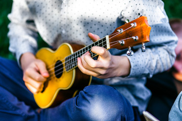 Man playing acoustic guitar close up outdoors