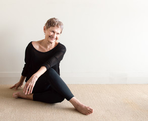 Older woman in black yoga clothing laughing in relaxed seated yoga posture