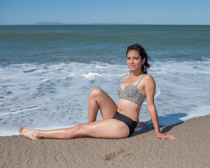 California Latina girl reclined in wet sand.
