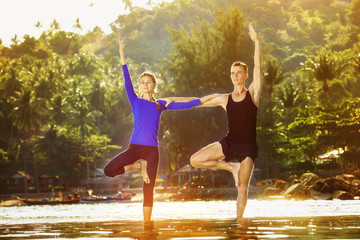 Young couple is practicing yoga at golden sea sunrise background