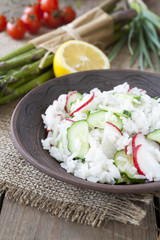 Risotto with fresh cucumber and radishes around fresh green asparagus spears
