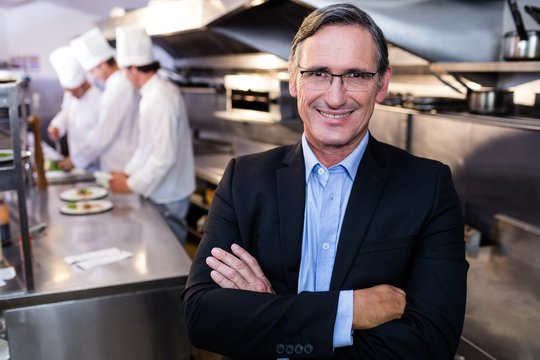Male restaurant manager standing with arms crossed