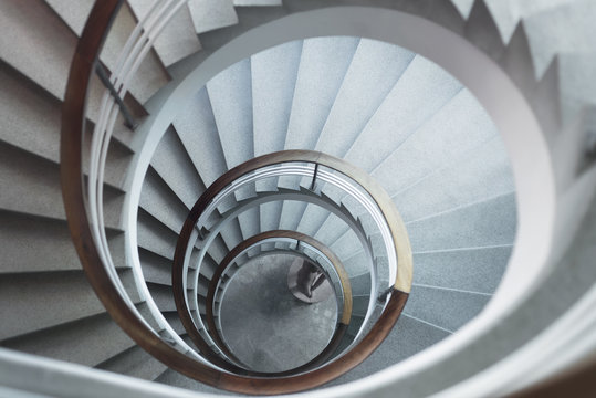 White spiral staircase in soft light with wooden banister looking down from above.