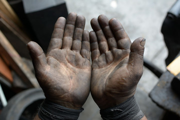 Worker hand covered with oil point of view