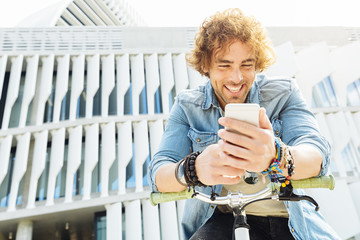 Portrait of Handsome young man smiling when he is using his mobi