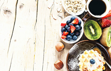Breakfast- cup of coffee with homemade belgian waffles, berries, hazelnuts, kiwi and oat flakes on wooden table with copy space. Selective focus.