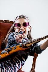 little girl playing as a guitar hero rockstar