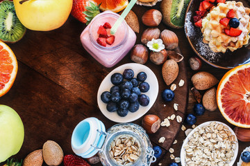 Health and colorful breakfast - with oat flakes, waffles, muffins,almond,hazelnuts,various fruits, berries and milk on old wooden table. Health food concept  .Top view.