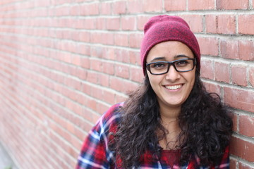 Close up studio portrait of cheerful brunette hipster girl making happy face. Brick urban wall background.