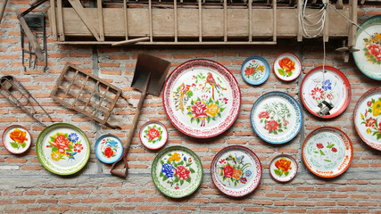 local Traditional Thai metal tray decorate on brick wall