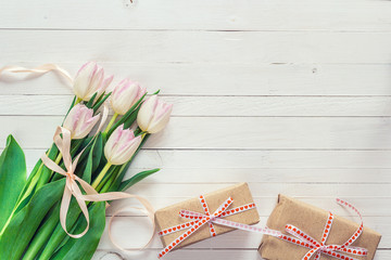 Pink tulips with rosy ribbon and gift boxes on a white painted w