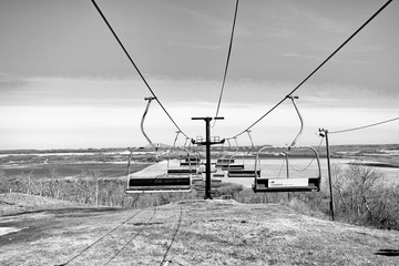A deserted ski lift over a valley in a black and white spring landscape