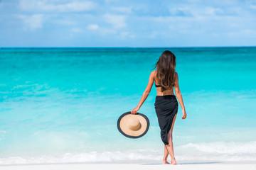 Woman in black bikini and sarong standing on beach