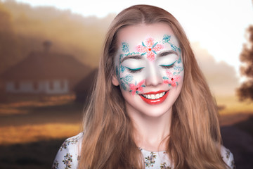 Portrait of beautiful young girl (woman lady model) painting, art expressionism, realistic flowers on white face. Bright creative makeup, expressive eyes, paint, colorful red green composition