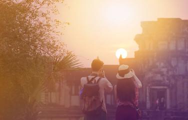 asian couple traveler photographing temples at  Angkor Wat,  com