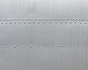 Abstract metallic texture. Silver metal background with rivets.