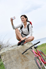 Woman on biking day taking picture with smartphone