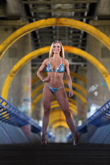 Sexy female bodybuilder in bikini standing on a bridge